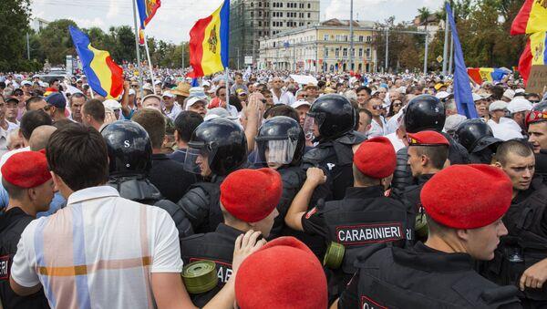 Сотрудники правоохранительных органов и участники акции протеста, требующие отставки правительства, в Кишиневе. 26 августа 2018