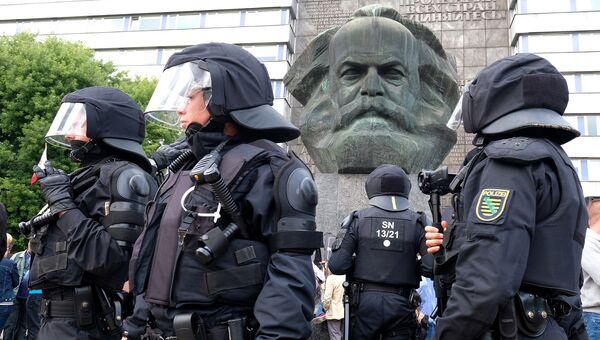 Полицейские рядом со скульптурой Карла Маркса во время беспорядков в Хемнице. Архивное фото