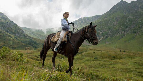 Туристка катается на лошади в Кавказском Государственном природном биосферном заповеднике