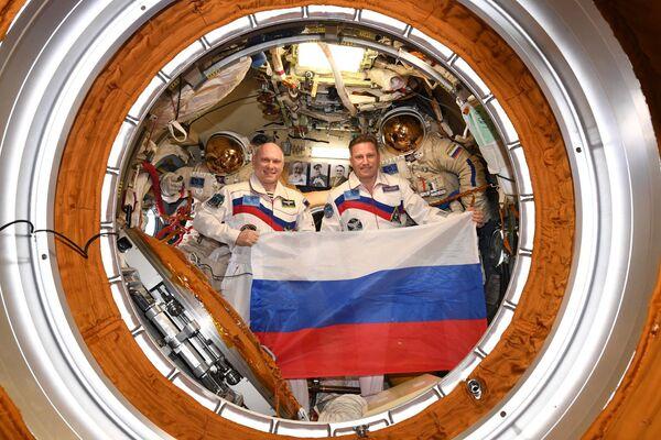 Российские космонавты Олег Артемьев и Сергей Прокопьев с флагом страны в День Государственного флага на борту МКС