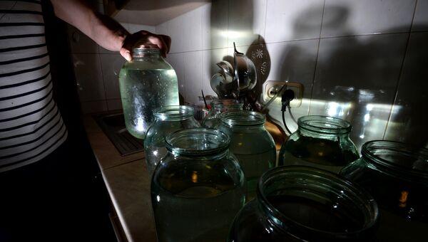 Житель Великого Новгорода набирает воду в банки