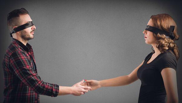Мужчина и женщина с завязанными глазами протягивают друг другу руку