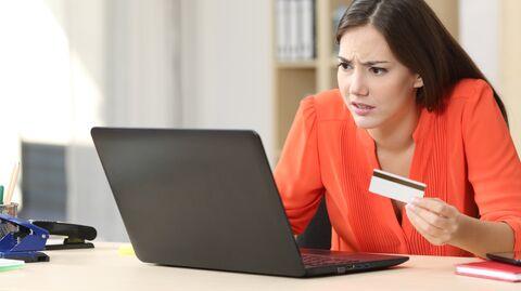 Девушка с банковской картой перед ноутбуком