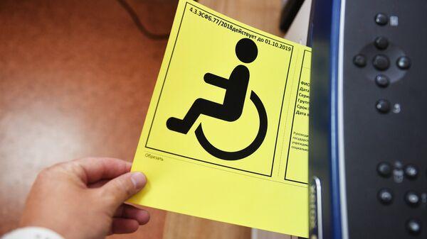 Сотрудник Федерального Бюро Медико-Социальной Экспертизы Министерства труда и социальной защиты РФ в Москве распечатывает опознавательный знак Инвалид