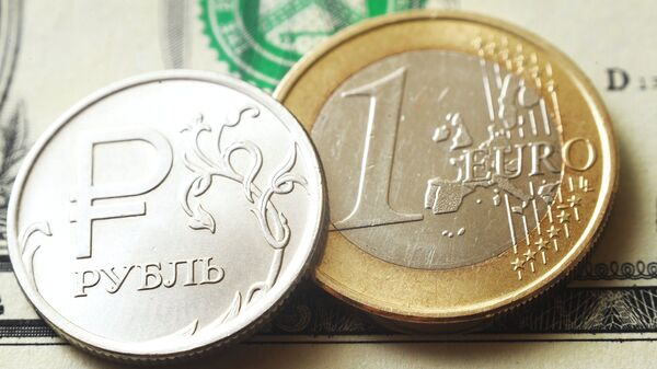 Монеты номиналом один рубль, один евро на банкноте один доллар США. Архивное фото