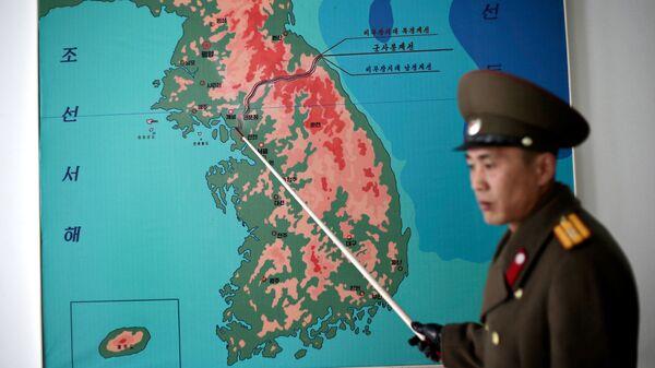 Северокорейский военный показывает на карте демилитаризованную зону на границе КНДР и Южной Кореи