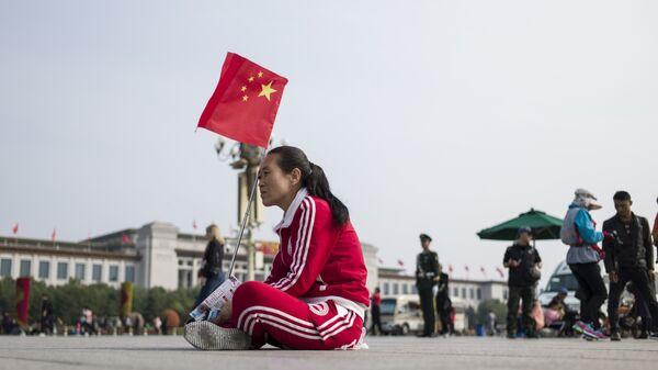 Женщина с флагом Китая на площади в Пекине