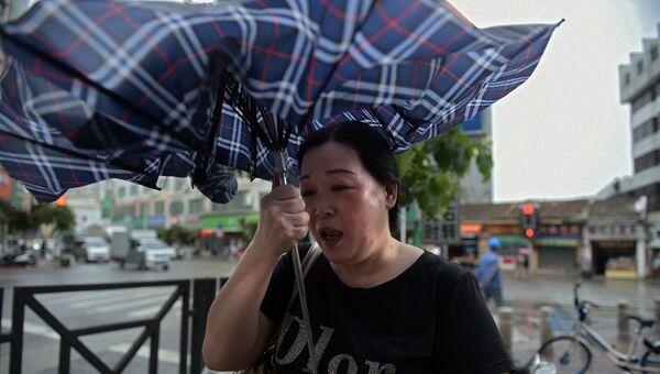 Женщина настигнута порывом сильного ветра, который связан с прибытием тайфуна Мангхута в город Янцзян южнокитайской провинции Гуандун. 16 сентября 2018
