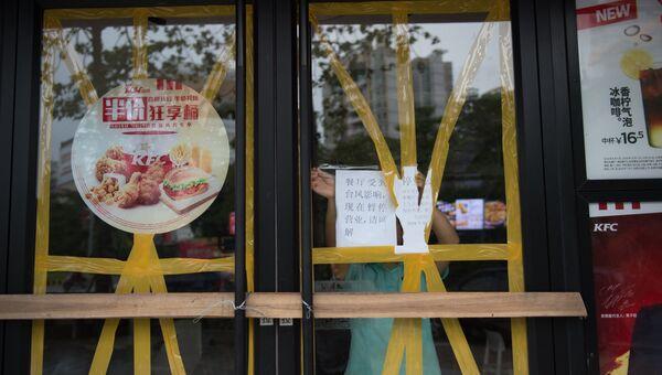 Работник закрывает ресторан перед прибытием супертайфуна Мангхут в Янцзяне в китайской провинции Гуандун, Китай. 16 сентября 2018 года