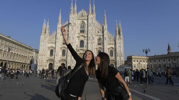 Туристы делают селфи перед собором Дуомо в Милане