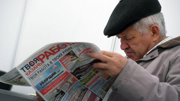 Посетитель с газетой Работа на ярмарке вакансий в Казани. Архивное фото