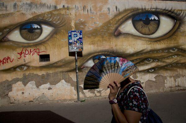 Женщина проходит мимо стрит-арта британского уличного художника My Dog Sighs в Риме