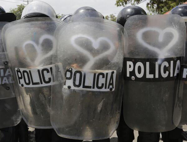 Граффити в вид сердец на полицейских щитах во время акций протеста против правительства президента Никарагуа Даниэля Ортега в Манагуа