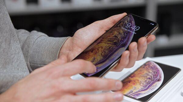 Посетитель рассматривает телефон iPhone XS Max в магазине re:Store в Санкт-Петербурге