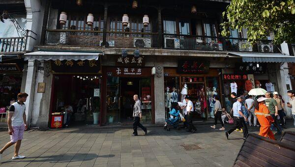 Прохожие на одной из улиц в городе Ханчжоу в Китае