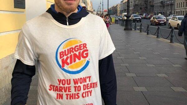 Промоутер компании Burger King в рекламной футболке с надписью В этом городе вы не умрете от голода на улице в Санкт-Петербурге. Архивное фото