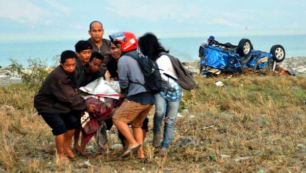 Люди помогают пострадавшему после землетрясения и цунами поразившего город Палу на острове Сулавеси, Индонезия. 29 сентября 2018