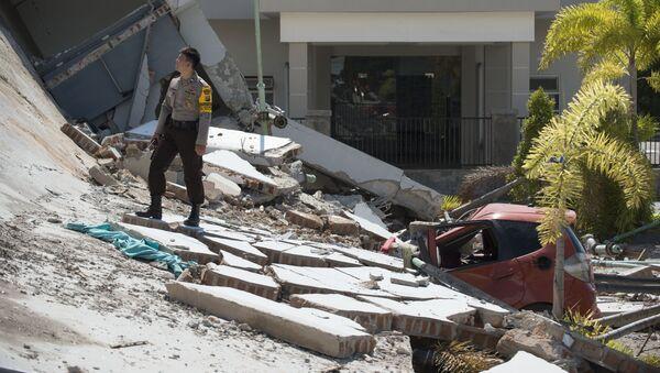 Полицейский на развалинах десятиэтажного отеля в Палу на острове Сулавеси, после того как он рухнул в результате сильного землетрясения, Индонезия. 30 сентября 2018