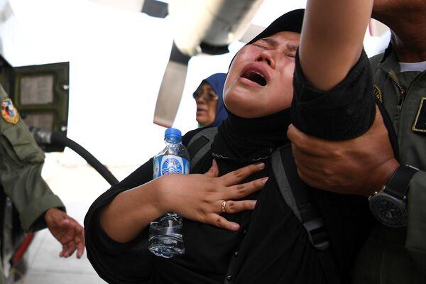 Женщина ожидает эвакуацию после землетрясения и цунами в аэропорту города Палу, остров Сулавеси, Индонезия. 30 сентября 2018