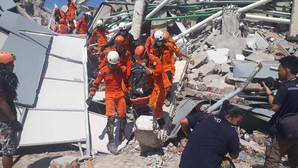 Сотрудники Humas Basarnas на месте рухнувшего отеля в Палу на острове Сулавеси, Индонезия. 30 сентября 2018 года