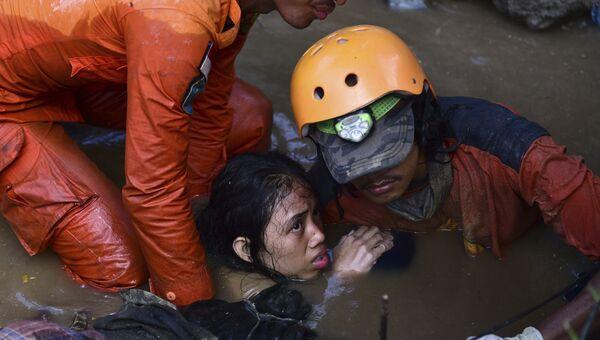 Cпасатели достают девушку из воды после землетрясений и цунами в городе Палу на острове Сулавеси в Индонезии. 30 сентября 2018 года