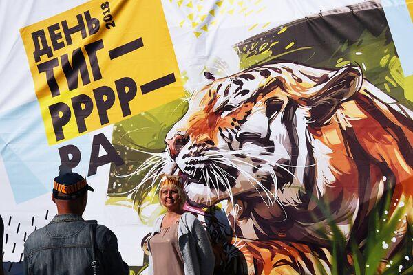 Отдыхающие фотографируются на фоне баннера с тигром на праздничных мероприятиях, посвященных Дню тигра, во Владивостоке