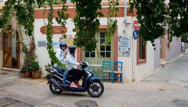Юноша с девушкой едут на мопеде по улице города Малия