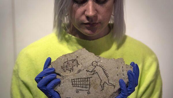 Сотрудница Национального музея Британии держит работу Бэнкси под названием Пекхамский камень