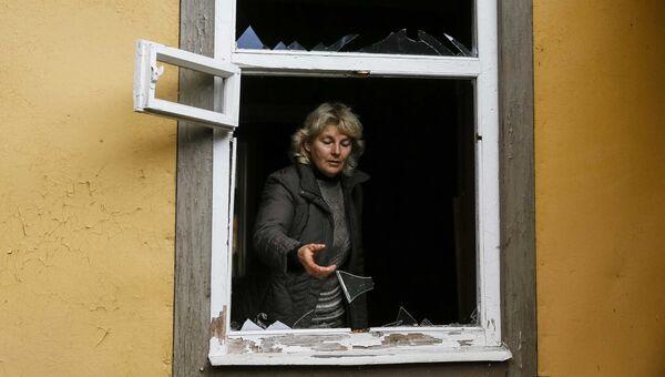 Местная жительница осматривает окно, выбитое в результате взрыва на военном складе в Черниговской области. 9 октября 2018