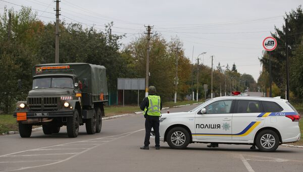 Сотрудники полиции Украины останавливают автомобили на дороге в Черниговской области после взрыва на военном складе. 9 октября 2018