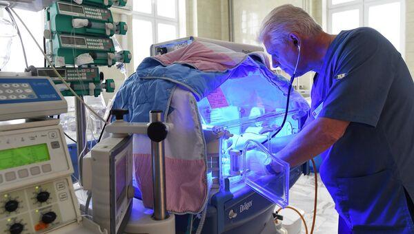 Врач осматривает глубоко недоношенного ребенка, подключенного к аппарату искусственной вентиляции легких, в детском отделении реанимации клиники акушерства и гинекологии имени В. Ф. Снегирева МГМУ имени И. М. Сеченова