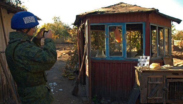 Сотрудник Совместного центра контроля и координации режима прекращения огня изучает последствия обстрела поселка Марьевка в Луганской области. 14 октября 2018