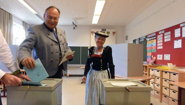 Местные жители в традиционной баварской одежде на избирательном участке в Нойкирхене, Германия. 14 октября 2018