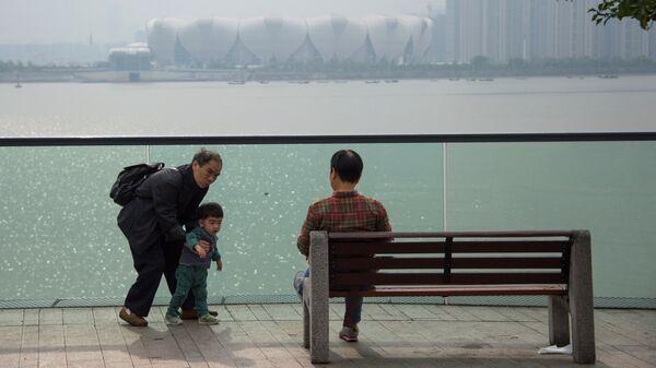 Жители на набережной в городе Ханчжоу в КНР