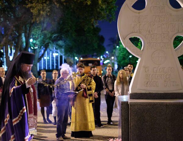 Священнослужитель читает молебен у импровизированного мемориала в Краснодаре в память о погибших при нападении на керченский колледж