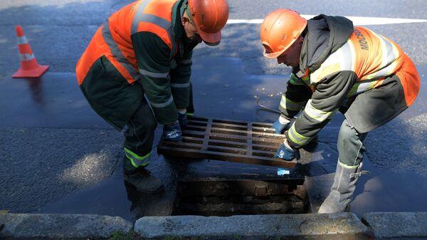 Сотрудники ЖКХ ведут работы по очистке от мусора ливневой канализации в Москве.