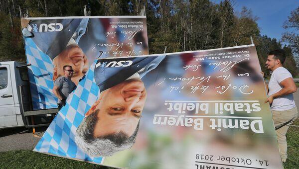 Уборка предвыборных плакатов с портретом политика Маркуса Зедера, члена партии ХСС. Зонтхофен, Бавария