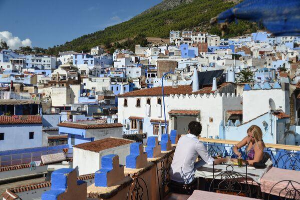 Люди в кафе на крыше одного из домов в городе Шефшауэн, Марокко