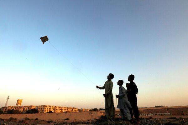Мальчики запускают воздушного змея в Карачи, Пакистан. 23 октября 2018 года