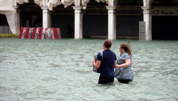 Люди на затопленной площади Святого Марка во время сезонного половодья в Венеции, Италия. 29 октября 2018 года