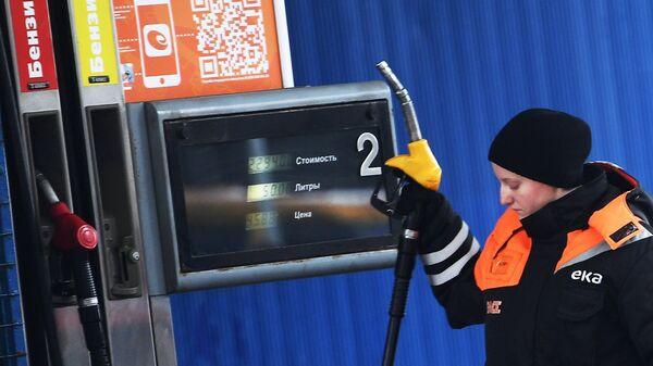 Рабочая у заправочной колонки на автозаправочной станции в Москве