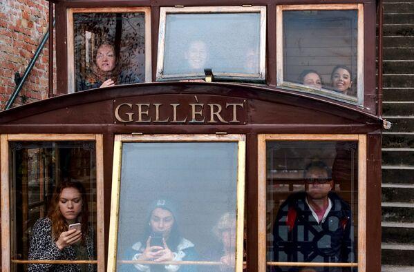 Туристы в вагончике Будайского фуникулера Шикло в Будапеште