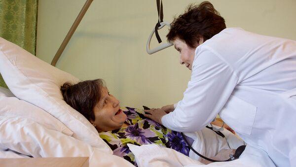 Медицинский работник осматривает пенсионерку. Архивное фото