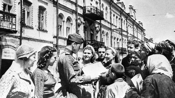 Советский солдат показывает жителям освобожденного Минска газету Правда