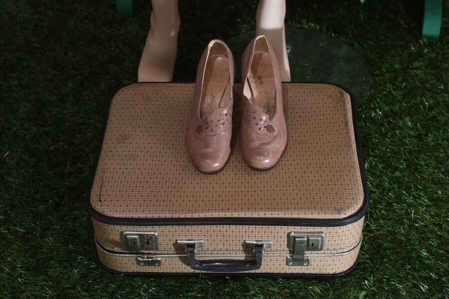 Чемодан и женские туфли. Экспонаты выставки «Путешествия как искусство»