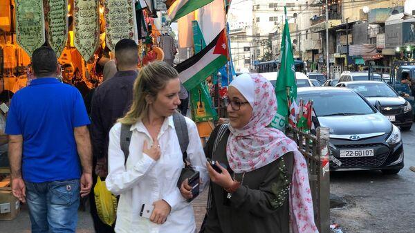 Женщины идут рядом с торговыми рядами по улице Аммана, Иордания