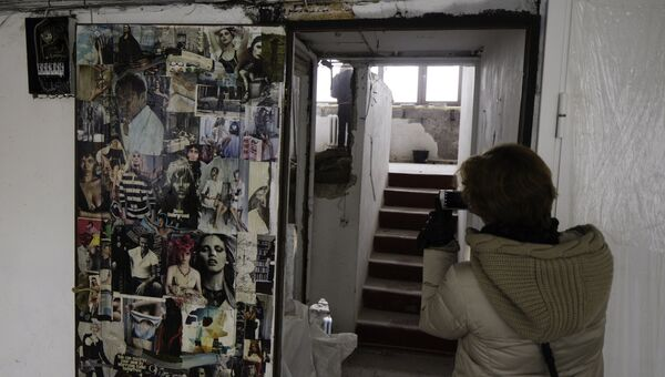 Девушка фотографирует во время экскурсии в Жилой Дом Наркомфина