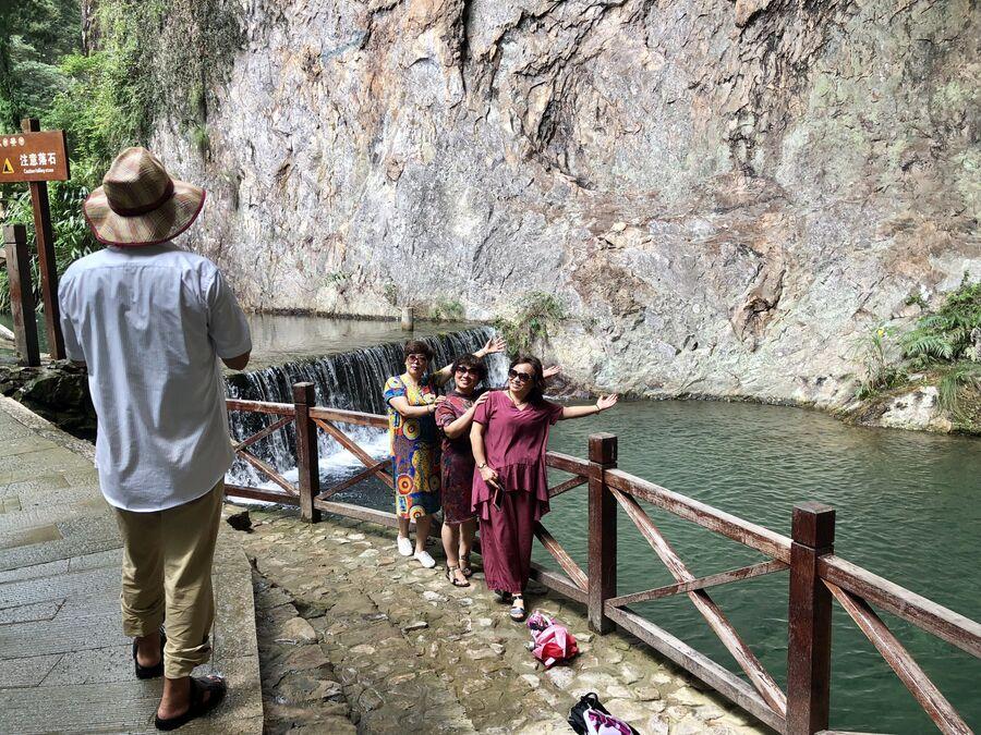 Китайские туристы позируют для фото в парке Яньданшань, Чжэцзян, Китай