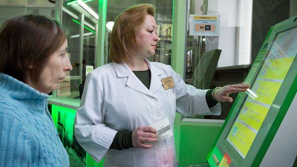 Сотрудница поликлиники помогает пациентке оформить талон на прием к врачу