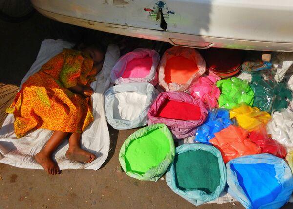 Ребенок спит рядом с сумками с цветным порошком на рынке в Нью-Дели, Индия. 4 ноября 2018 года